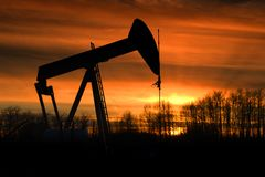 Sunset Pumpjack. A pumpjack silhouette against a blazing sunset royalty free stock photo