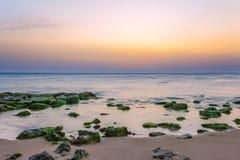 Sunset at Punta Secca Beach - Montalbano Filming Location. Sunset at Punta Secca Beach with rocks and green seaweeds in Santa Croce Camerina, Sicily, Italy royalty free stock image