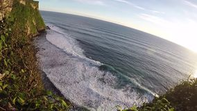 Sunset at Pura Uluwatu. Ocean waves and top view. Bali, Indonesia. Slowmo stock footage