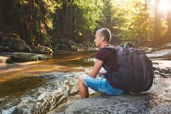 Sunset in pure nature. Traveler with backpack resting on the riverside in forest. National park Krkonose, Czech Republic Stock Photography