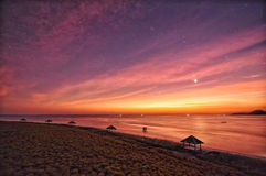 Sunset purple skies on the beach ocean honey moon wide Stock Photo
