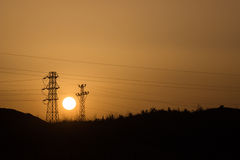 Sunset and pylons. Electricity cables, pylons and sunset Stock Images