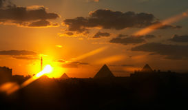 Sunset of a pyramid and mosque. Pyramids and a mosque on a background of a sunset with the cloudy sky Stock Images