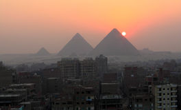 Sunset and the pyramids. Sun setting over the pyramids of Giza Royalty Free Stock Photos