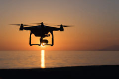 The sunset and the quadcopter. Over the sea Royalty Free Stock Photo