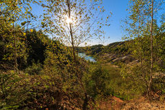 Sunset at quarry or lake or pond with sandy beach, green water,. Birch on a foreground and hills with blue sky at summer season Royalty Free Stock Images