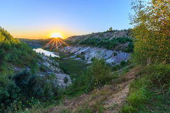 Sunset quarry or lake or pond with sandy beach, green water, tre. Sunset at quarry or lake or pond with sandy beach, green water, trees and hills with blue sky Stock Photo