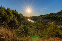 Sunset quarry or lake or pond with sandy beach, green water, tre. Sunset at quarry or lake or pond with sandy beach, green water, trees and hills with blue sky Stock Photos