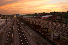 Sunset Rails. A railyard at sunset, with an approaching train royalty free stock image