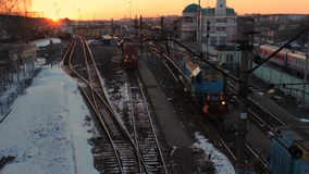 Sunset on railway station. locomotive cargo trains rail lines, snow winter time. Russian railways stock footage