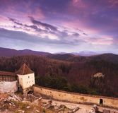 Sunset at Rasnov medieval citadel in Transylvania. Panoramic view of the defense wall and mountains in the horizon. Panoramic view of the defense wall of Rasnov stock images