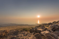 Sunset and ray path at the top of Antelope Island with rocks at the foreground Royalty Free Stock Images