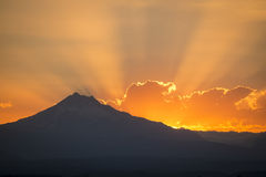 Sunset rays behind silhouette of mountain Royalty Free Stock Images