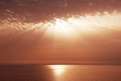 Sunset rays and clouds over sea Royalty Free Stock Photo