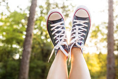 Sunset rays throug the legs in sneakers Stock Image