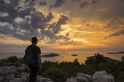 Man standing outdoor on mountain with backpack looking at sunset over sea in Croatia Europe. Sunset Razanj Croatia. Beautiful nature and landscape photo. Nice Stock Image
