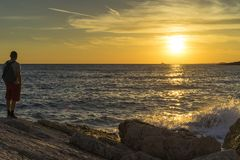 Man standing outdoors at coast looking at sun going down over the sea stock photo