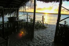 Sunset at Real River, Bahia, Brazil. Sunset at Real river, Mangue seco village,  Bahia, Brazil, view from inside a simple straw house stock photo