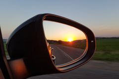 Sunset in the rearview mirror of a black car. Side mirrors. Sunset in the rearview mirror of a black car. Side mirrors royalty free stock image