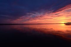 Sunset red glow over the lake late in the summer evening Stock Photography
