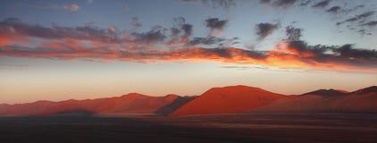 Sunset and red sand dune, Namib desert, Namibia. Panoramic view of sunset and red sand dune, Namib desert, Sossusvlei, Namibia Stock Photos