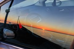 The sunset is reflected in car glass Royalty Free Stock Image