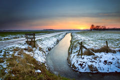 Sunset reflected in frozen canal Royalty Free Stock Image