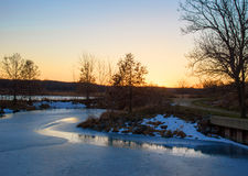 Sunset reflected in ice covered pond along walkway Royalty Free Stock Photo