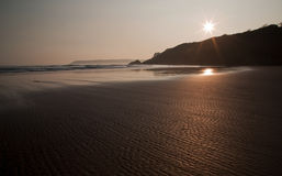 Sunset reflected in the ripples and wet sands of Threecliff Bay, The Gower, South Wales Royalty Free Stock Photography