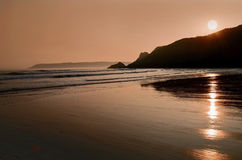 Sunset reflected in the ripples and wet sands of Threecliff Bay, The Gower, South Wales Stock Images