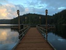 Sunset reflecting on a calm lake with deck in the foreground Royalty Free Stock Photography