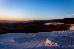 Beatiful sunset in Pamukkale valley. Sunset reflecting over the beautiful white stone cascade in the Pamukkale Royalty Free Stock Images