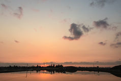 A sunset reflecting over the lake with clouds Royalty Free Stock Photography