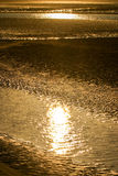 Sunset reflecting on sand beach Royalty Free Stock Image