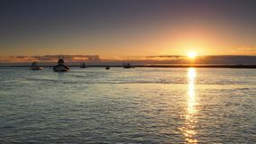 Sunset reflecting in the sea with small fishing boats anchored in calm water, Orford, Suffolk stock image