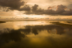 Sunset reflection. The cloudy sunset reflecting in the pool of water during low tide royalty free stock image
