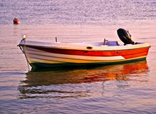 Sunset reflection of a fishing boat on sea Royalty Free Stock Photography