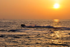 Sunset reflection on the sea. And jet-ski sport activity Stock Images