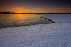 Sunset reflection and snowy ice. Royalty Free Stock Photography
