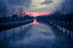 Sunset reflection in water at dawn. On a winter day the sun is going down Stock Images