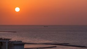 Sunset in Ajman from rooftop timelapse. Ajman is the capital of the emirate of Ajman in the United Arab Emirates. Sunset with reflection in water of Gulf in stock images