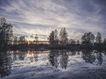 Sunset reflection in water - vintage look edit. Landscape reflection in a lake on calm autumn night - vintage look edit Stock Photo