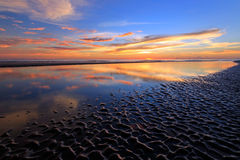 Sunset reflection with wavy sand patterns Stock Photos
