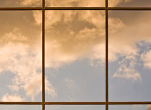 Sunset reflections. Clouds lit by the setting sun reflecting in a modern office building windows Royalty Free Stock Image