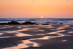 Sunset reflections on Porthtown Beach. Bright orange setting sun reflects in the meandering rivulets of water on Porthtowan Beach in Cornwall, UK Royalty Free Stock Image