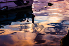 Sunset Reflections On Sea Water. Reflections of the sunset on the surface of a sea water with a rowboat with its anchor rope Stock Photos