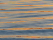 Sunset reflections on water. Reflections of sunset light on the surface of the lake Stock Images