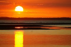 Sunset Reflections in Water. A sunset occurs when the sun descends below the horizon and the light of the day slowly fades. This happens at different times Stock Photo