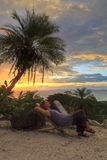 Sunset Relaxation. A beautiful woman relaxes under a plam tree on a poolside beach overlooking the Pacific Ocean and Nicoya Peninsula at sunset near Tarcoles Stock Images