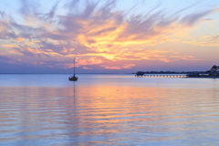 Sunset Remnants. A sailboat silhouetted against the sky reflected in the quiet waters of a cove off Pensacola Bay, Florida Royalty Free Stock Photo